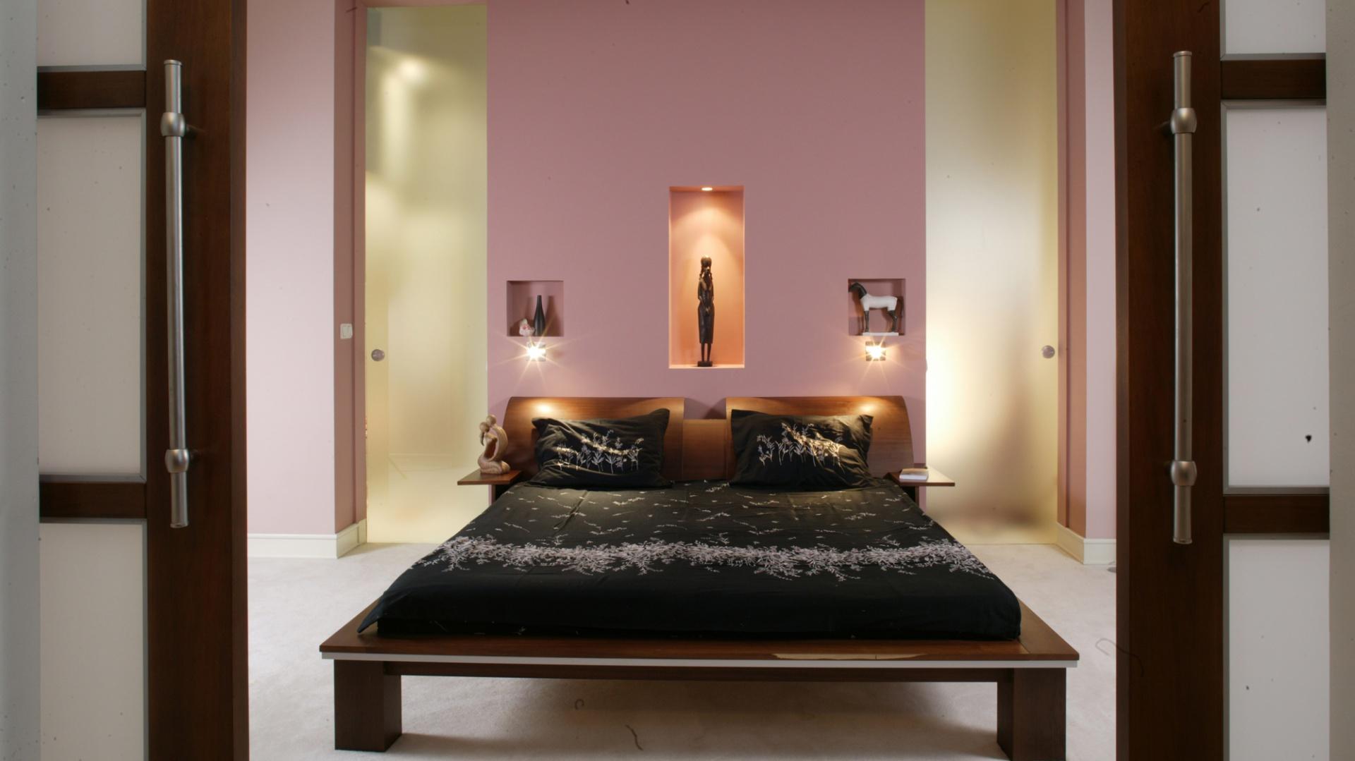 Nad zagłówkami łóżka wykonano we wnęce trzy półki. Największa jest oświetlona w środku, a pod mniejszymi zamontowano maleńkie lampki.