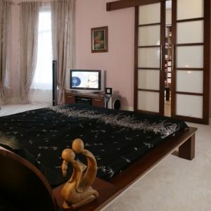 Z sypialni do garderoby prowadzą piękne, biało-brązowe drzwi, współgrające z orzechowym łóżkiem. Ich wzornictwo zostało zainspirowane Japonią.