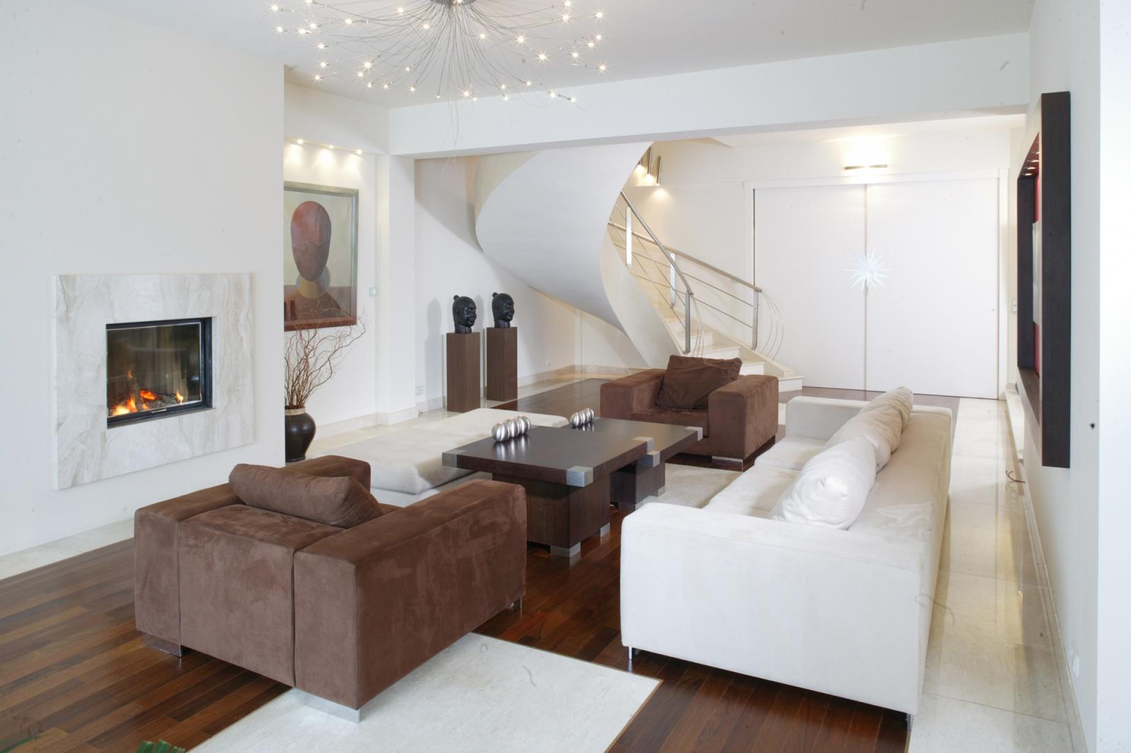 Eleganckie schody, wychodzące wprost z salonu, prowadzą do nocnej części domu. Są one obłożone kamieniem w tym samym kolorze, co kwadraty w parkiecie salonu. Fot. Marcin Onufryjuk.