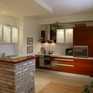 Kuchnia jest dużym, otwartym wnętrzem. Jej wizualną odrębność wyznaczają murek z cegieł oraz podwieszany fragment sufitu z regularnie rozmieszczonymi halogenami. Fot. Tomek Markowski.