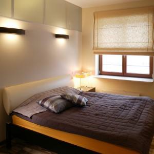 Duża szafa z jasnobrązowego forniru to – oprócz łóżka – jeden z niewielu mebli w sypialni. Oryginalny wygląd zapewnia jej mocny element – poprzeczny, czarny pas ze skóry. W oknie rzymska roleta z surowego, półtransparentnego płótna. Fot. Tomek Markowski.