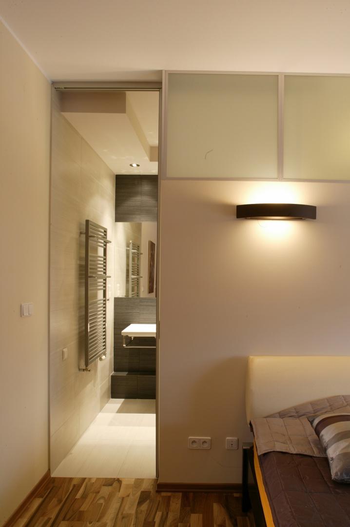 Centralnym punktem oszczędnie urządzonej sypialni jest duże łóżko z szerokim zagłówkiem (Bo Concept). Sztuczne oświetlenie zapewniają nocne lampki z pomarańczowymi abażurami i czekoladowe kinkiety umieszczone na ścianie. Fot. Tomek Markowski.