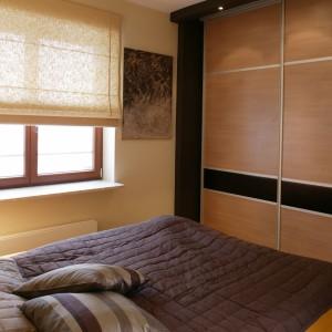 Sypialnia łączy się z łazienką, do której prowadzą szklane drzwi. Razem ze szklanym świetlikiem umieszczonym w górnej części ściany, drzwi tworzą odwróconą literę L. Fot. Tomek Markowski.