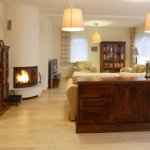 Z obitego lnem kompletu wypoczynkowego roztacza się widok na całe mieszkanie: otwarty ogród zimowy, jadalnię, hol i kuchnię.