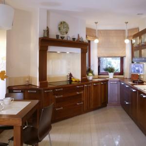 Duża kuchnia, ulokowana na powierzchni o ciekawym kształcie klina, otwarta została na jadalnię, hol i pokój dzienny. Zamontowane tuż przy oknie wiszące lampki wizualnie skracają przestrzeń, przybliżając najdalej wysuniętą część do środka. Fot. Tomasz Markowski.