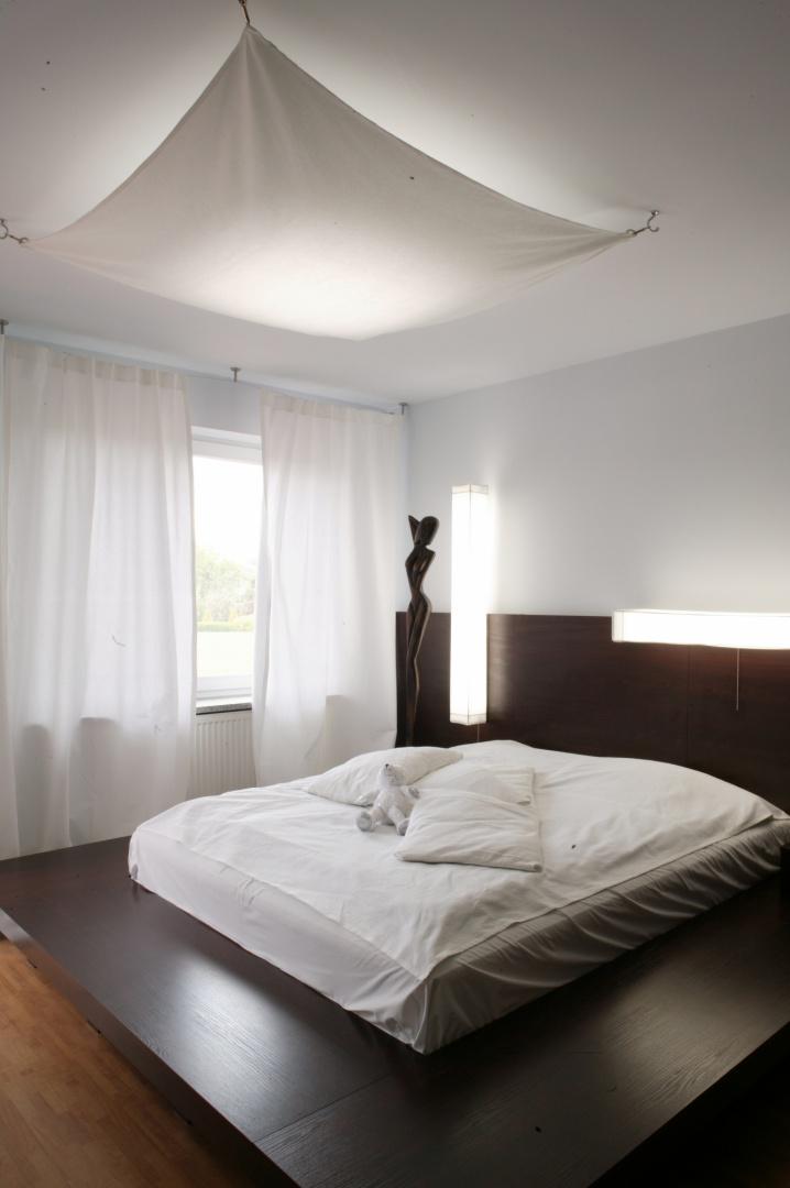 Wyposażenie sypialni to stylistyczna symbioza kształtów i monochromatycznych kolorów. Śnieżnobiała  pościel mocno odcina się od ciemnej oprawy łóżka, które dzięki ogromnemu podestowi wypełnia niemalże całe wnętrze. Fot. Monika Filipiuk.