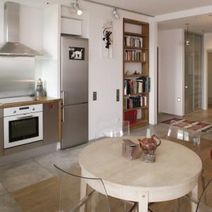 Dębowy stół, podobnie jak podłoga w salonie, został pobielony. Czerwone kanapy i fotele ożywiają i przydają wnętrzu przytulności. Fot. Monika Filipiuk.