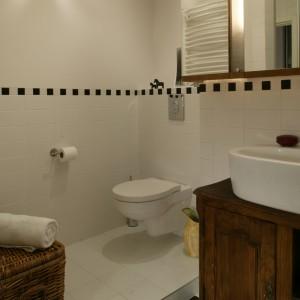 """Drewniane elementy (szafka pod umywalką oraz wykonany z tego samego materiału dekor pod lustrem) ocieplają wnętrze łazienki. Również wiklinowy kosz na bieliznę nawiązuje do """"przemyconej"""" tu stylistyki retro. Fot. Monika Filipiuk."""