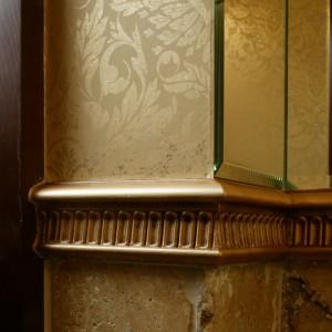 Różne okładziny ścian: kamienne kafle, tekstylne tapety oraz lustra, łączy ceramiczna listwa, ręcznie złocona i spatynowana. Fot. Monika Filipiuk.