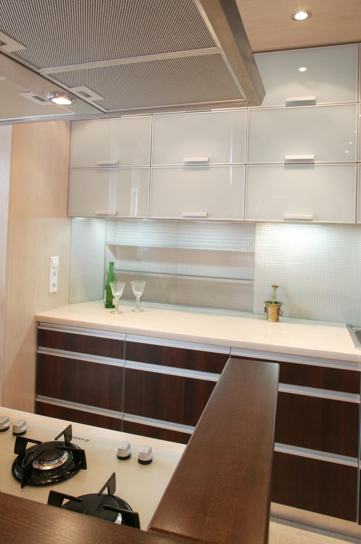 Strefa kuchenna wydaje się niezwykle uporządkowana, a dzięki pojemnej zabudowie na niewielkiej przestrzeni można pomieścić wszystkie kuchenne akcesoria. Fot. Tomasz Markowski.