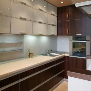 Wiszące szafki, z frontami wykonanymi z barwionego na kremowo szkła, oraz liczne szuflady, zostały rozmieszczone w kuchni w równych, proporcjonalnych rzędach. Fot. Tomasz Markowski.
