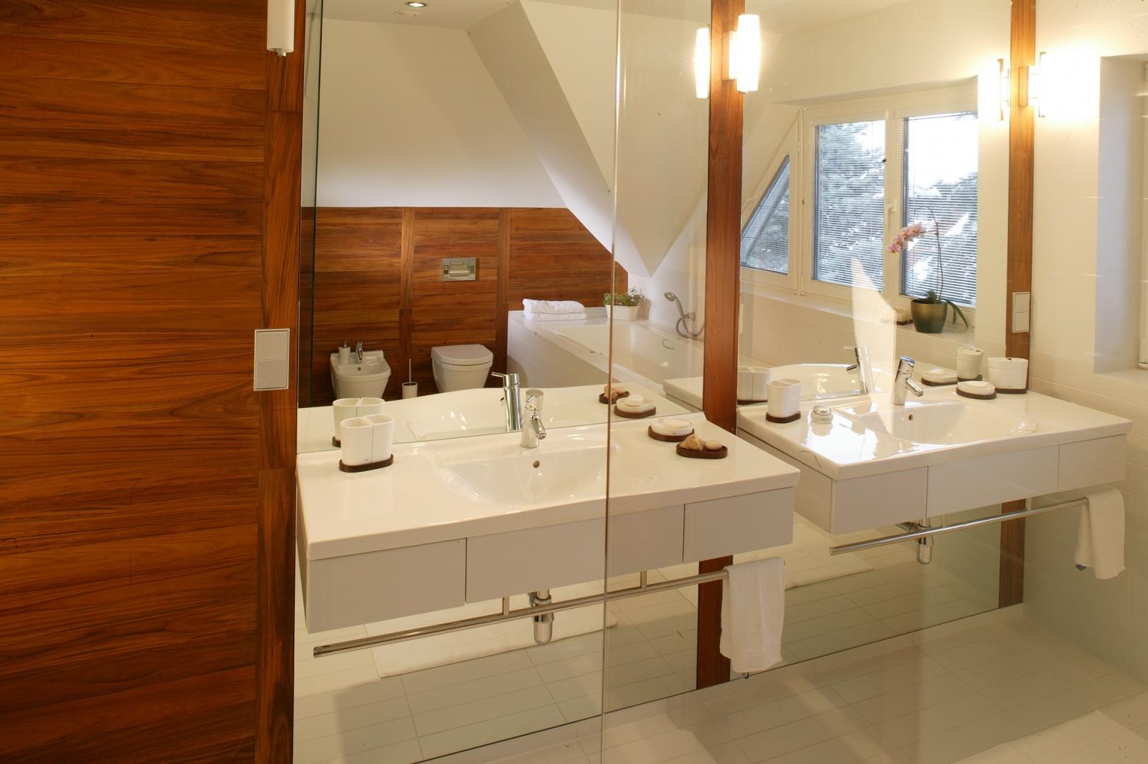 Dwie geometryczne umywalki doskonale wpisują się w minimalistyczną formę wnętrza. Umieszczono je na tafli lustra i wyposażono w relingi ze stali nierdzewnej, do zawieszania ręczników. Fot. Marcin Onufryjuk.