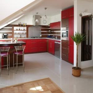 Elementem, który w najbardziej widoczny sposób określa charakter przestrzeni kuchennej jest wyrazisty kolor czerwieni. Barwa ta została zestawiona z jasną podłogą oraz drewnianymi i aluminiowymi wstawkami w ścianie. Fot. Monika Filipiuk.