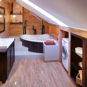 """Skosy poddasza wykorzystano niezwykle funkcjonalnie. W najwyższej części łazienki zamontowano szafkę z umywalką, w najniższej zaś wannę, pralkę i rząd półek na przybory. Tak plastyczne """"manipulowanie"""" przestrzenią, z niewygodnych skosów poddasza, uczyniło jego atut. Fot. Monika Filipiuk."""