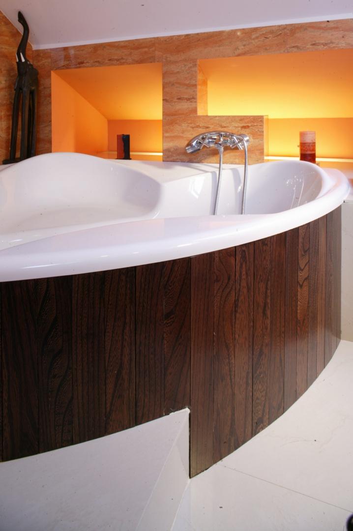 Fragment ściany za wanną pokrywa ażurowa konstrukcja wykonana z kilku podświetlanych nisz. Sączące się z nich delikatne światło buduje nastrój w tej części łazienki, uprzyjemniając długie chwile kąpieli. Fot. Monika Filipiuk.