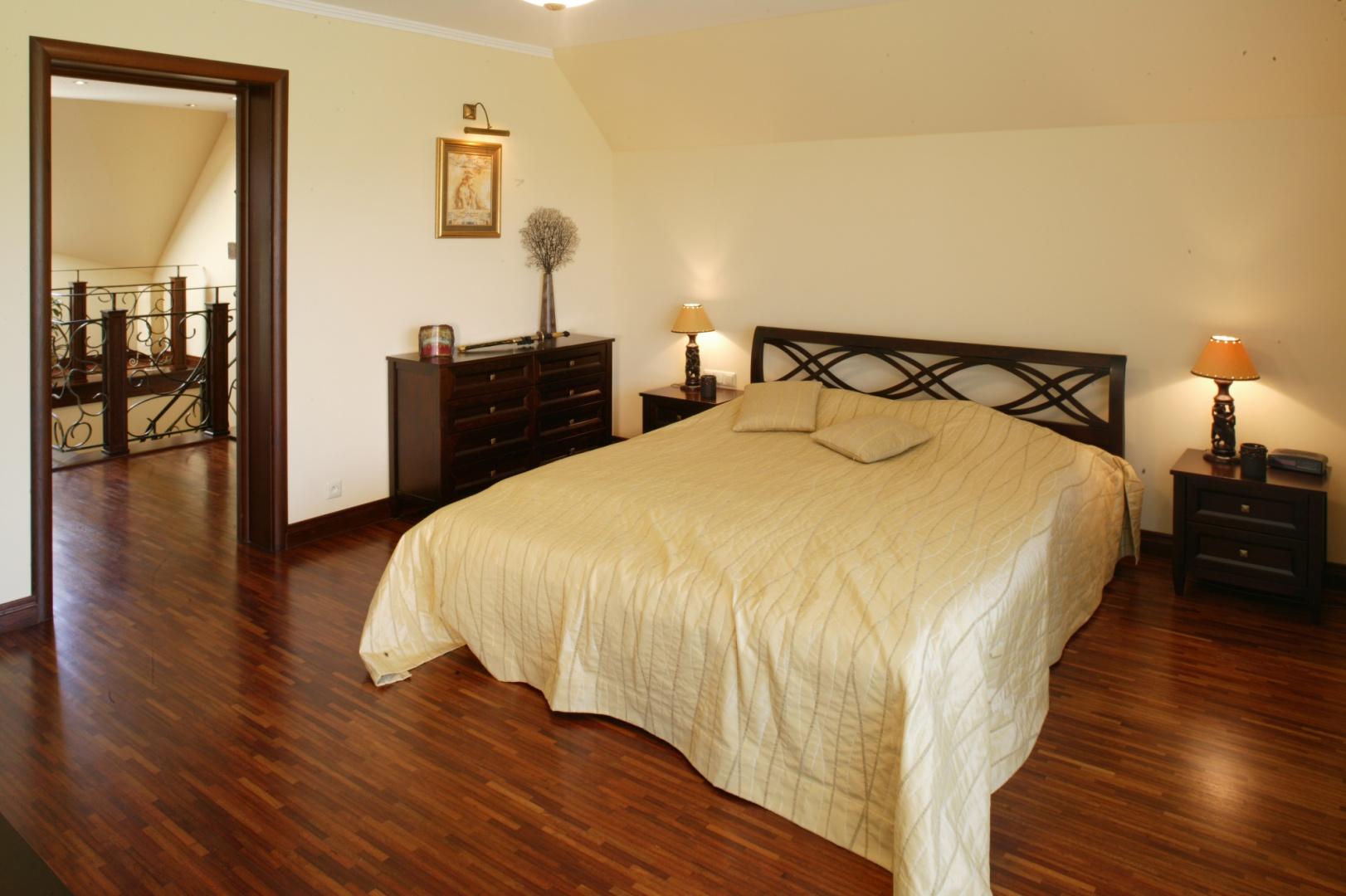 Sypialnia została zaaranżowana w ciepłych barwach. Centralne miejsce zajmuje tu duże łóżko z oryginalnym, jakby plecionym zagłówkiem. Towarzyszą mu ciemne, niezbyt masywne meble. Fot. Monika Filipiuk.