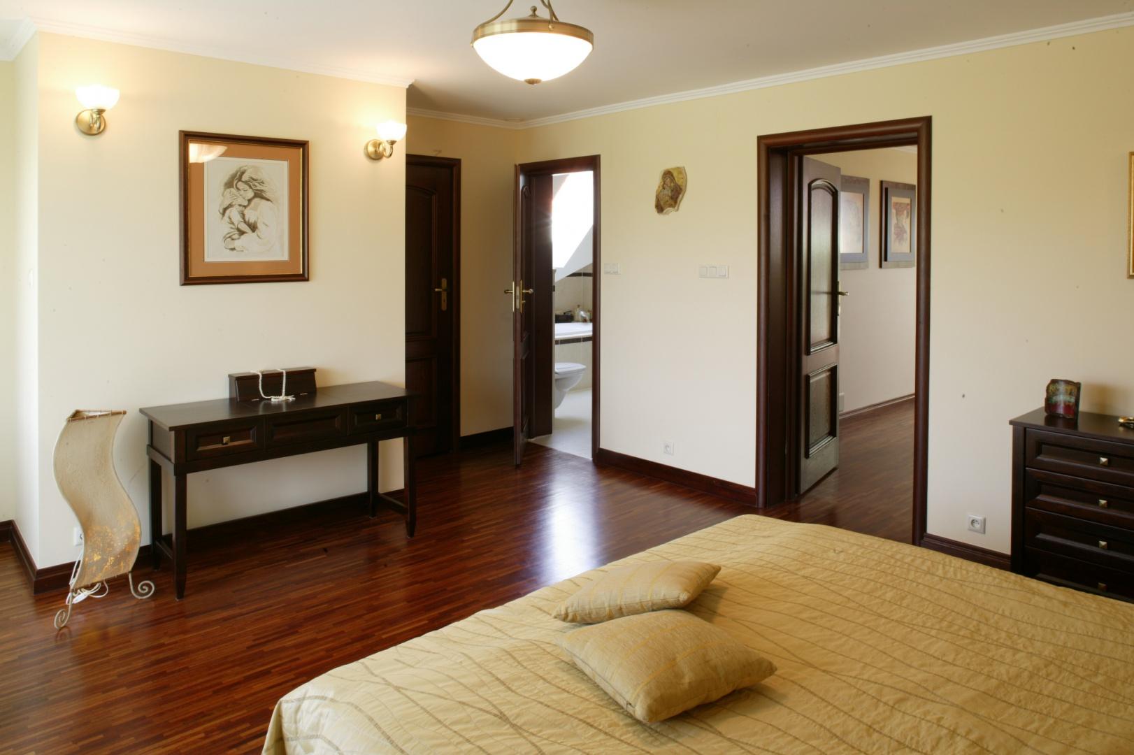 Sypialnia, podobnie jak cały hol na piętrze, wyłożona została przemysłowym parkietem merbau w drobne paski. Z pomieszczenia prowadzi troje drzwi: na korytarz, do prywatnej łazienki oraz do garderoby. Fot. Monika Filipiuk.