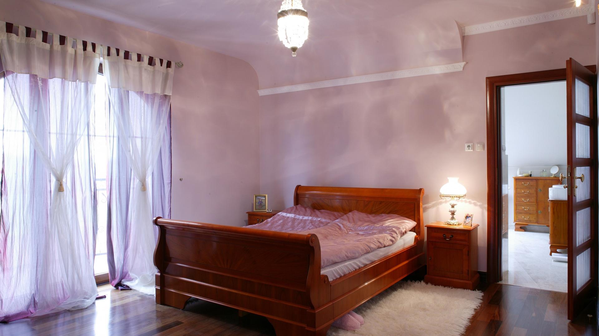 Zwracają uwagę ścielące się na podłogę tiulowe firany czy, nawiązujące skojarzenia z baldachimem, lekkie obniżenie sufitu nad łóżkiem.