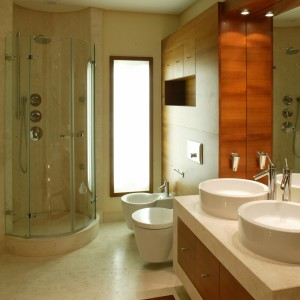 O ostatecznym, dostojnym wyglądzie wnętrza zadecydowały geometryczne, uporządkowane linie mebli łazienkowych oraz ceramiki, a także naturalne materiały wykończeniowe. Fot. Tomasz Markowski.