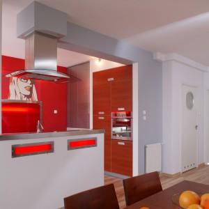 Elektryzującą czerwień projektantka wnętrza zestawiła z szarością. Pojawia się ona nie tylko na ścianach. Neutralna barwa występuje też na obudowie okapu i aranżacji okna, którą kolorystycznie równoważy stół o barwie czereśni. Fot. Tomasz Markowski.