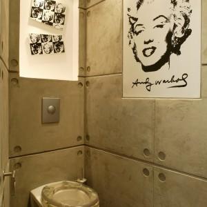 Zimne, betonowe ściany architekci zdecydowali się połączyć z pięknem Marylin Monroe, które wyraźnie kontrastuje z syntetycznie zimnym i prostym w swoim wyrazie sedesem. Fot. Marcin Łukaszewicz.