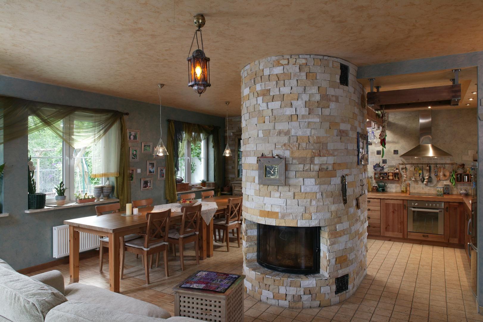 Centralnym punktem kuchni jest owalny kominek – wyłożony kamieniem, niczym kaflowy piec. Fot. Tomasz Markowski.