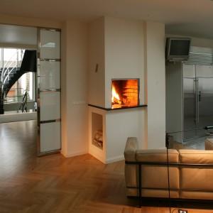 Na granicy przestrzeni kuchennej i strefy wypoczynkowej, tuż za przesuwnymi drzwiami, znalazło się miejsce dla kominka, który do minimalistycznego wnętrza wnosi nie tylko odrobinę ciepła, ale także służy właścicielom domu do wypieku chleba. Fot. Tomasz Markowski.