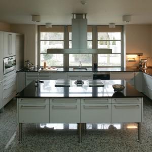 W centralnym miejscu kuchni znajduje się wyspa wyposażona w trzy różnego rodzaju płyty modułowe. Elementem wieńczącym całość jest stalowy okap, którego oszczędna, prosta linia nawiązuje do stylistyki mebli. Fot. Tomasz Markowski.