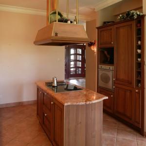 W centrum nowocześnie rozplanowanej kuchni znajduje się wyspa z marmurowym, łososiowym blatem i wmontowaną nowoczesną, szklaną płytą kuchenną. Fot. Tomasz Markowski.