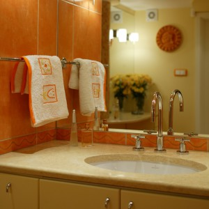 Pomieszczenie służy nie tylko do relaksu i marzeń sennych w kąpieli. Toaletkę z granitowym blatem i ogromnym lustrem stworzono z myślą o kobiecie, która ma wygodne miejsce do pielęgnowania swojej urody. Fot. Marcin Łukaszewicz.