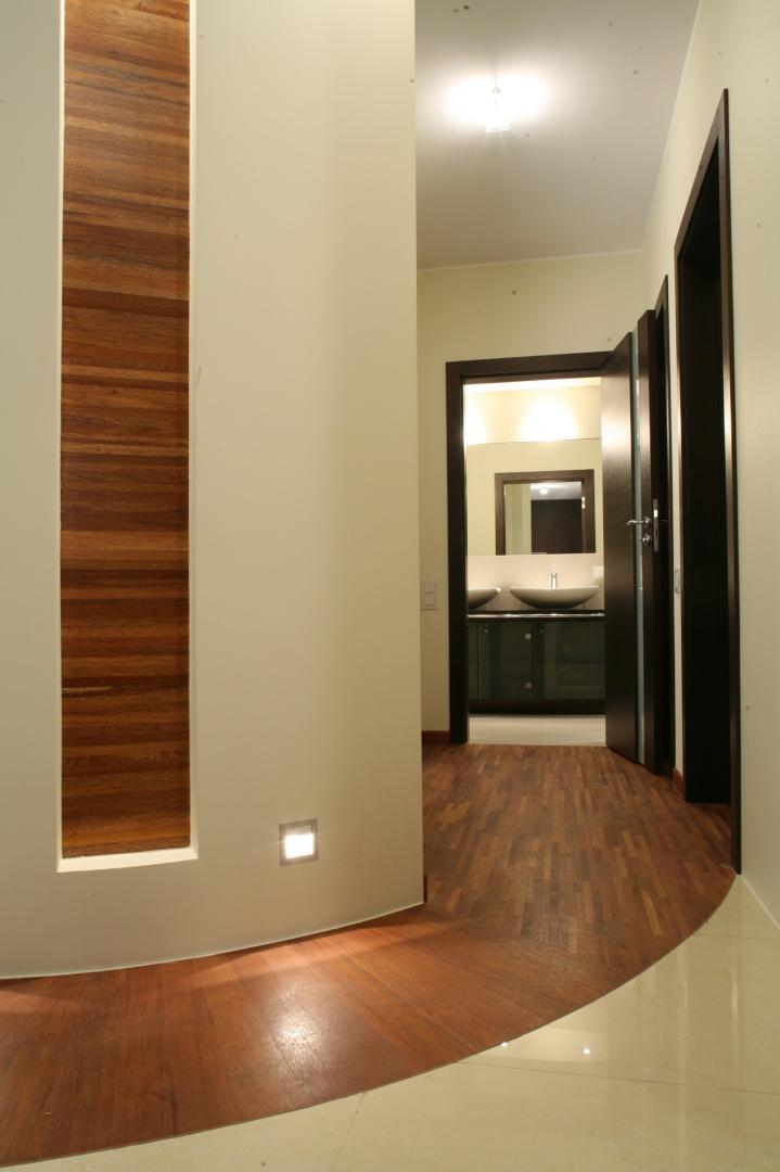To jedyna łazienka w mieszkaniu. Prowadzi do niej wejście z holu. Kolor parkietu przemysłowego merbau stanowi wdzięczny kontrast dla odcieni beżów i ciemnego wenge. Fot. Bartosz Jarosz.