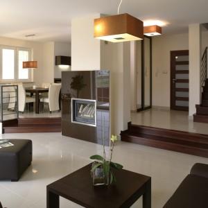 Podłoga z beżowego chińskiego gresu polerowanego oraz drewniane elementy wykończeniowe stanowią doskonałe tło dla brązowych mebli i kominka. Fot. Bartosz Jarosz.