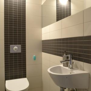 Toaleta kontynuuje królujący na parterze stylistyczny minimalizm. Jej wystrój bazuje na trzech, stonowanych kolorach: od naturalnej bieli (zlew i sedes, Keramag), po  duże płytki w kolorze ecru i mniejsze grafitowe. Fot. Bartosz Jarosz.