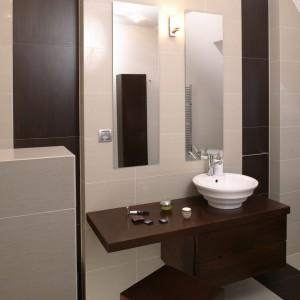 W łazience zastosowano dwa rodzaje płytek: beżowy gres, doskonale imitujący trawertyn oraz płytki, które kolorem i fakturą przypominają drewno wengé. Fot. Bartosz Jarosz.