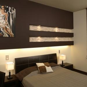 Efektowna zabudowa na głównej ścianie sypialni, to pomalowana na czekoladowy kolor konstrukcja z gipsokartonu. Jak widać, jej dekoracyjne możliwości zostały wykorzystane w każdym calu. Fot. Bartosz Jarosz.