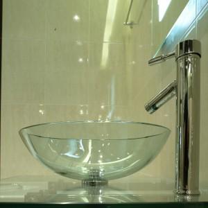 Przydał się dobór lekkich, przezroczystych detali, takich jak: oryginalnie podświetlone lustro oraz szklana umywalka, oparta na szklanym blacie, z wykończeniami z chromowanej stali. Fot. Monika Filipiuk.
