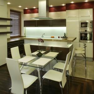 Jadalnia ze szklanym blatem i delikatnymi, kremowymi krzesłami, to kontrast dla dość ciężkiego umeblowania salonu, a zarazem nawiązanie do minimalistycznego designu kuchni, urządzonej w kremowym mdf-ie i dębowym fornirze. Fot. Bartosz Jarosz.