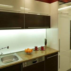 Mleczne szkło przyklejone na ścianie nad blatem roboczym oświetlają zainstalowane pod wiszącymi szafkami świetlówki. Całość robi wrażenie świecącej lampy. Fot. Bartosz Jarosz.