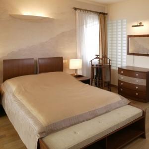 W sypialni, tak jak w łazience, dominują odcienie ciepłych, naturalnych brązów. Ściana za łóżkiem wyrasta z drewnianych powierzchni niczym fragment antycznego muru, ze śladami cegieł i spękanego tynku. Fot. Monika Filipiuk.