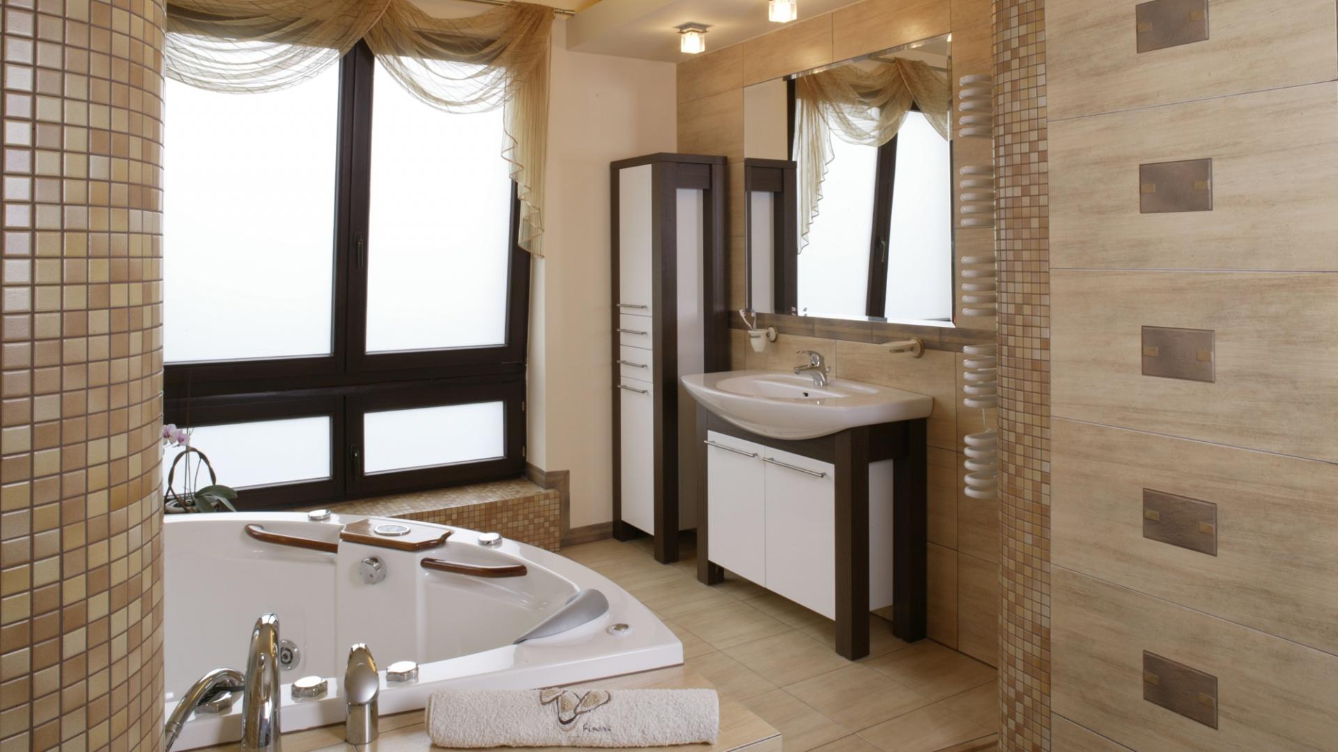 Łazienkowe meble wykonane są z zestawionych na prawach kontrastu materiałów: ciemnego drewna wenge i białej, laminowanej płyty. Szafki znajdują się nie tylko w strefie umywalki, ale także obok kabiny prysznicowej. Fot. Monika Filipiuk.