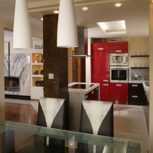 Z jadalni dobrze widać kominek w salonie. Jego obudowę tworzą dwie identyczne płyty marmuru, które spotykają się ze sobą na zasadzie lustrzanego odbicia. Fot. Bartosz Jarosz.
