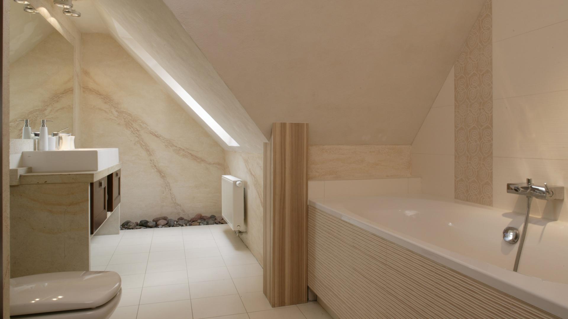 Jasna, przytulna łazienka to także wyraźne nawiązanie do natury. Wszystkie płytki mają podobny, subtelny odcień ecru. Ściany i podłoga zostały wyłożone płytkami z kolekcji Nirvana, hiszpańskiej marki Saloni. Fot. Bartosz Jarosz.
