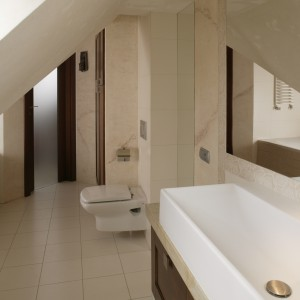 Nie tylko sufit, ale i obrys wnętrza łazienki malowniczo rozrzeźbiają skosy i uskoki ścian. Fot. Bartosz Jarosz.