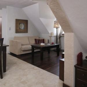 Dolna część mieszkania została wyłożona dwoma rodzajami podłogi: drewnem i płytkami. W części wypoczynkowej – parkietem z ciemnego palisandru, interesująco mieniącym się odcieniami butelkowej zieleni. Fot. Bartosz Jarosz.
