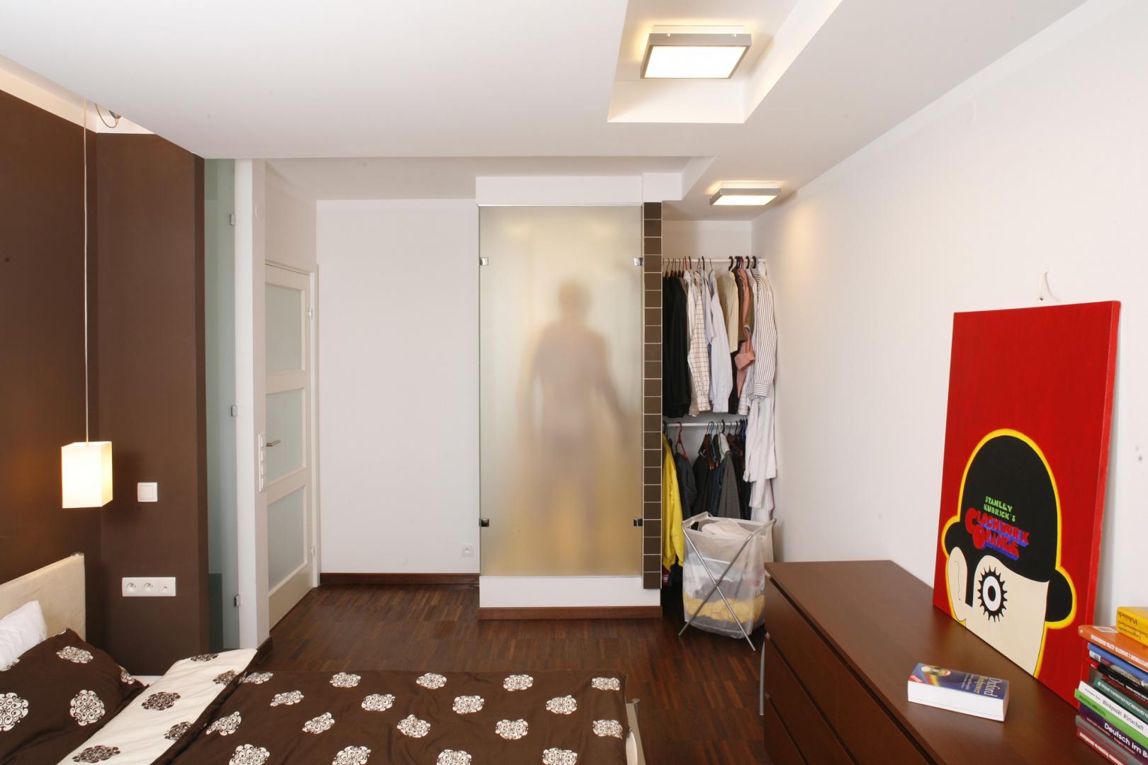 Zaaranżowana w odcieniach bieli i brązu męska sypialnia, to miejsce bardzo intrygujące... Przede wszystkim za sprawą oryginalnego rozwiązania – wprowadzenia do sypialni części kabiny prysznicowej z przyległej łazienki. Fot. Bartosz Jarosz.