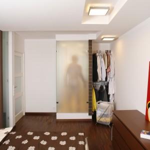 Męska sypialnia, zaaranżowana w odcieniach bieli i brązu, to miejsce intrygujące. Przede wszystkim za sprawą oryginalnego rozwiązania – wprowadzenia do sypialni części kabiny prysznicowej z przyległej łazienki. Fot. Bartosz Jarosz.