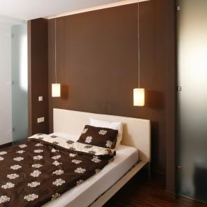 Czekoladowa ściana utworzyła rodzaj okazałego, królewskiego wezgłowia łóżka. Nad całkiem sporym, wykonanym z jasnego drewna meblem zawisły dwie bliźniacze lampy. Fot. Bartosz Jarosz.