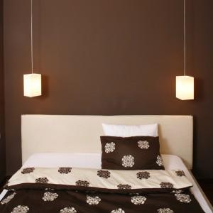 Ściana w kolorze czekolady utworzyła rodzaj okazałego wezgłowia łóżka. Nad sporym, wykonanym z jasnego drewna meblem zawisły dwie bliźniacze lampy. Fot. Bartosz Jarosz.