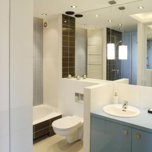 Niebagatelną rolę w percepcji łazienki odgrywają lustra, które zajmują całą ścianę naprzeciw i nad umywalką. Zwielokrotniona w ten sposób przestrzeń zdaje się nie mieć granic. Fot. Bartosz Jarosz.