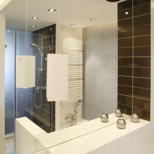 """W sporym lustrze odbija się cała łazienka, zarówno matowe, jak i lśniące powierzchnie, w tym """"wędrująca"""", obudowana mlecznym szkłem kabina prysznicowa. Łazienkowa ceramika to firma Koło, baterie – Grohe. Fot. Bartosz Jarosz."""